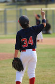 Youth ballplayer holding up finger. — Stock Photo