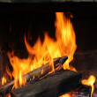 Fire in the old stone fireplace — Stock Photo #38796429