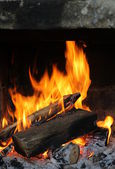 Fire in the old stone fireplace — Stock Photo
