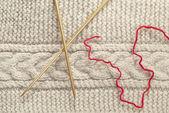 Piece of knit fabric and knitting needle — Stock Photo