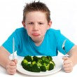 Grumpy young boy not happy about eating broccoli. — Stock Photo