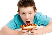 Joven hambre comiendo un hot dog. — Foto de Stock