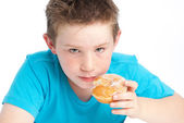 Youny boy eating a sugary doughnut. — Stock Photo