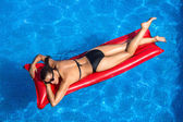 Beauty Brunette Sunbathing in the Pool — Stock Photo