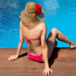 Beauty Woman Sitting on edge of Swimming Pool — Stock Photo #31315935