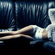 Beautiful blonde woman on black couch   — Стоковая фотография