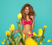 Beautiful blonde woman in pink swimsuit and yellow tulips — Stock Photo