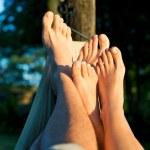 Foot of couple on hammock enjoying sun — Stock Photo #29273767