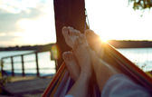 Vacation photo of couple feet relaxing on beach on hammock — Stock Photo
