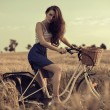 Stock Photo: Attractive woman with bike in wheat field
