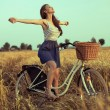 Free woman enjoying freedom on bike on wheat field at sunset — Стоковая фотография