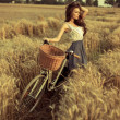 Stock Photo: Woman with bike resting on wheat field at sunset