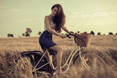 Attractive woman with bike in wheat field — Stock Photo