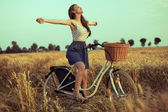Free woman enjoying freedom on bike on wheat field at sunset — Stock Photo