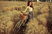 Kvinna med cykel vilar på vete fält vid solnedgången — Stockfoto