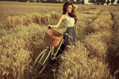 Woman with bike resting on wheat field at sunset — Stock Photo