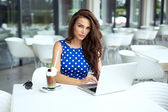 Beautiful woman working on laptop and drinking cafe — Stock Photo