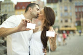 Kissing couple showing white card — Stock Photo