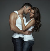 Sensual man hugging beautiful young woman — Stock Photo