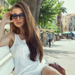 Young woman wearing sungasses and resting on bench — Stock Photo #32991239