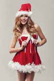 Happy woman in santa clause costume holding ribbon — Foto Stock