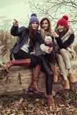 Happy tree girls wearing a woolly hats and showing something — Stock Photo