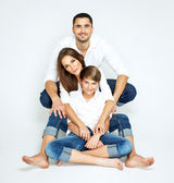 Young happy family on white background — Stock Photo