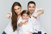 Portrait of happy family with pointing fingers — Stock Photo