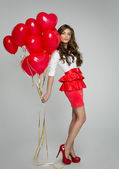 Beautiful woman with red balloons — Stock Photo