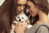 Beautiful women with a cute puppy — Stock Photo