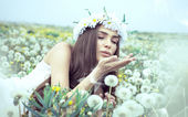 Woman blowing dandelions — Stock Photo
