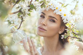 Woman pluck a perfume bottle from the tree — Stock Photo