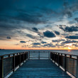 Backlit Pier at Sunset with Sun and Clouds - Stock Photo