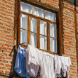 Old window in brickwork with hanging laundry — Stock Photo #40317877