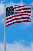American flag blowing in the wind with a blue sky background — Stock Photo