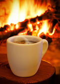 A cup of hot coffee in front of the fireplace — Stock Photo
