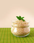 Quinoa in a glass bowl on green napkin — Stock Photo