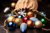 Christmas decorations spilled from canvas bag on a table — Stock Photo