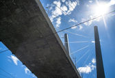 Cable-stayed bridge from below against a blue sky with clouds — Stock Photo