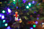 Christmas toy angel with a red heart in the hands hanging on the Christmas tree — Stock Photo