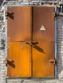 "Old rusty metal door to the substation with a ""cautiously electricity"" — Stock Photo"