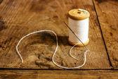 Bobina con fili bianchi e un ago bloccato — Foto Stock