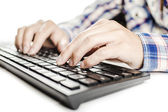 Woman in checkered shirt writing on a black keyboard — Stock Photo