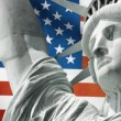 Statue of Liberty with US flag in background - Stock Photo