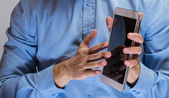 Man in blue shirt holding white tablet pc — Stock Photo