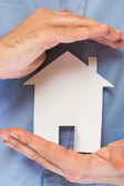 Man holding paper house in his hands — Stock Photo