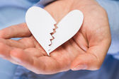 Hand with broken paper heart — Stock Photo