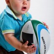 Baby boy with a rugby ball. — Stock Photo