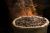 Sack full of still hot, freshly roasted coffee beans with the falling coffee beans. — Stock Photo