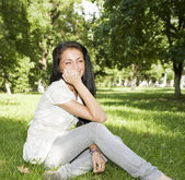 Cute girl sitting on the grass — Stock Photo